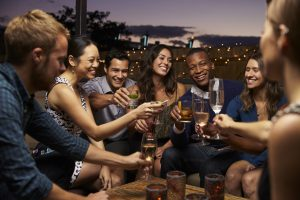 Group Of Friends Enjoying Night Out At Rooftop Bar